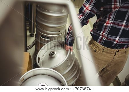 Midsection of manufacturer holding kegs in brewery