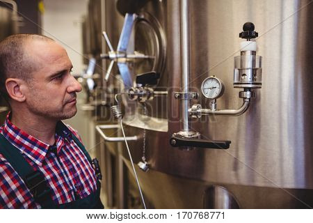 Male manufacturer looking at pressure gauge in brewery
