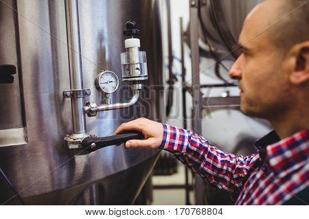 Male manufacturer adjusting pressure gauge in brewery