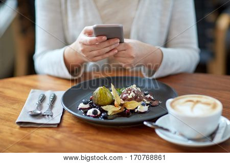 food, new nordic cuisine, technology, eating and people concept - woman with smartphone, chocolate ice cream dessert with blueberry kissel, honey baked fig and yoghurt and coffee sitting at cafe table