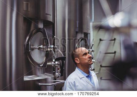 Manufacturer looking at storage tanks in distillery