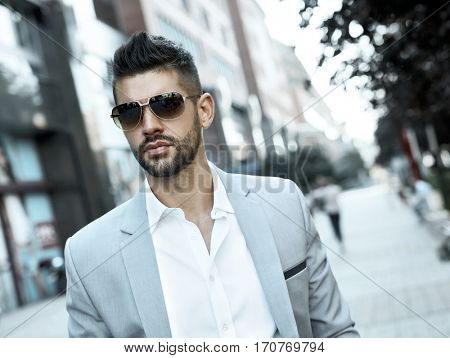 Successful dedicated young businessman on street wearing suit and sunglasses.