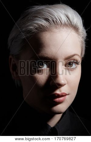 Artistic portrait of young woman with platinum blonde hair, looking at camera. Close-up photo.