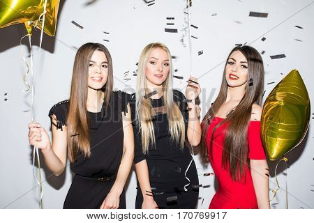women with star shaped balloons and confetti having party over white background