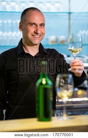 Portrait of waiter holding glass of white wine in restaurant