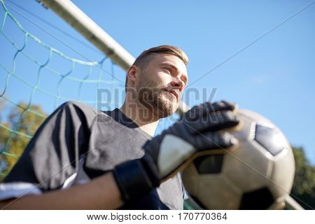 sport and people - soccer player or goalkeeper with ball at football goal on field