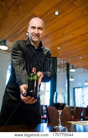 Portrait of waiter holding a bottle of red wine in restaurant