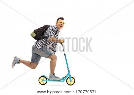 Full length portrait of an overjoyed guy riding a scooter and looking at the camera isolated on white background