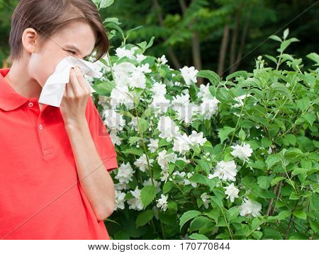 Teenager boy with hay fever blowing his nose allergic to bloom flowers in a spring garden
