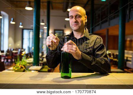 Waiter opening a bottle of white wine in restaurant