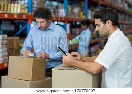 Focus of managers are working in the middle of cardboard boxes in a warehouse