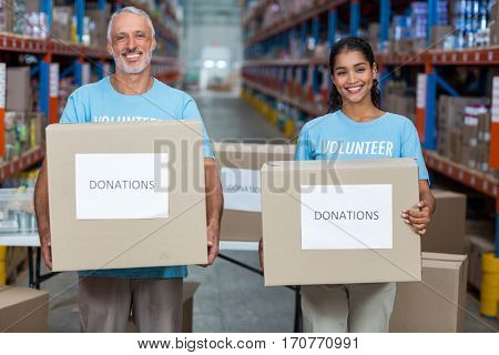 Happy volunteers are smiling and holding donations boxes in a warehouse