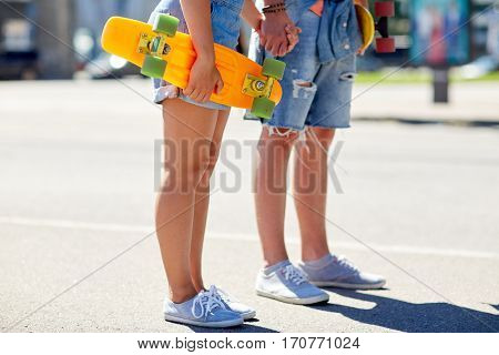 summer, relations, extreme sport and people concept - close up of happy teenage couple with short modern cruiser skateboards on city street