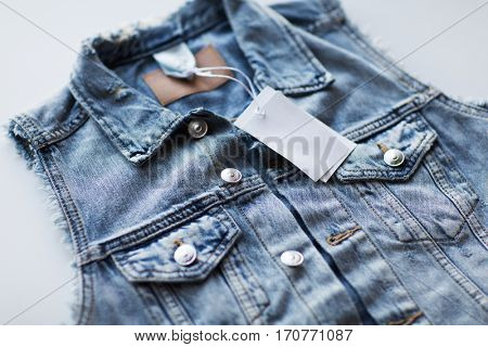 clothes, wear and fashion concept - close up of denim vest or waistcoat with price tag on white background