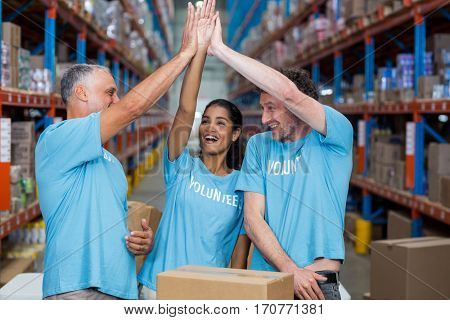 Happy volunteers are clapping hands each other in a warehouse