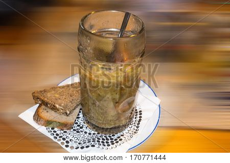 Homemade potato soup in beer glass against background with motion blur.