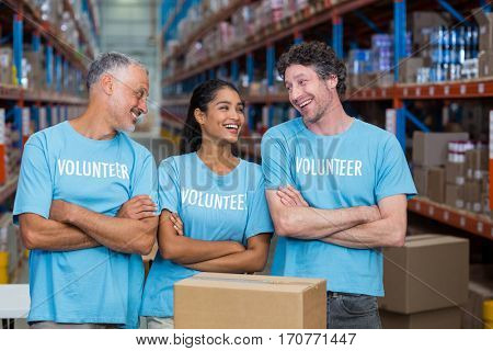 Happy volunteers are laughing and looking each other with crossed arms in a warehouse