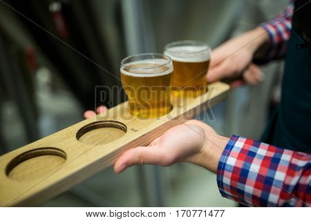 Close-up of brewer holding beer sampler tray at brewery factory