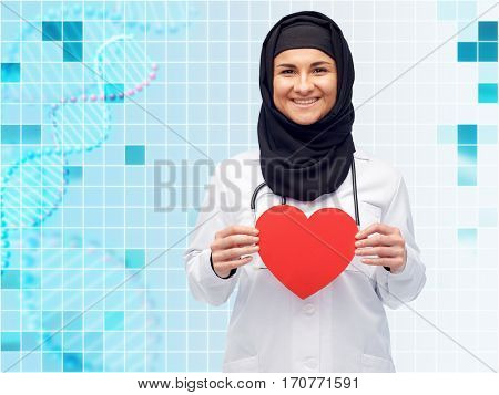 medicine, healthcare, charity and people concept - smiling muslim female doctor wearing hijab and white coat with red heart and stethoscope over blue background with grid and dna molecule