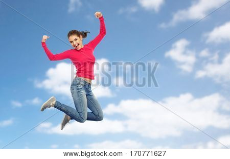 happiness, freedom, power, motion and people concept - smiling young woman jumping in air with raised fists over blue sky and clouds background