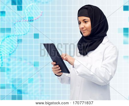 medicine, healthcare, technology and people concept - smiling muslim female doctor wearing hijab and white coat with tablet pc computer over blue background with grid and dna molecule