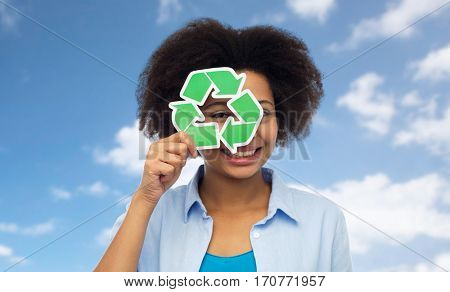people, ecology, conservation and recycling concept - happy african american young woman looking through recycle symbol over blue sky and clouds background