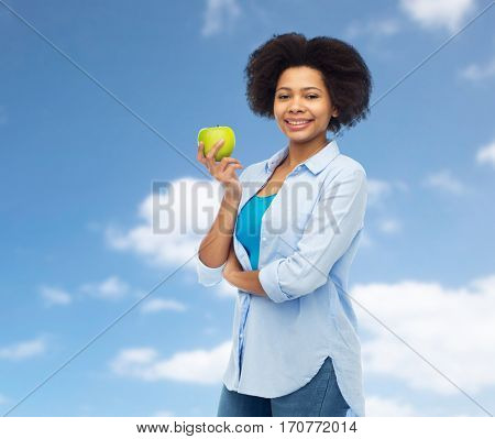 people, food, healthy eating and dental care concept - happy african american young woman with green apple over blue sky and clouds background