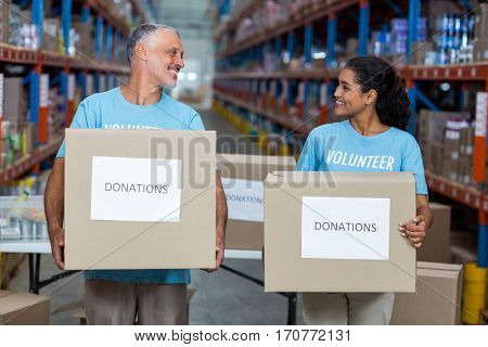 Happy volunteers are holding donations boxes and looking each other in a warehouse
