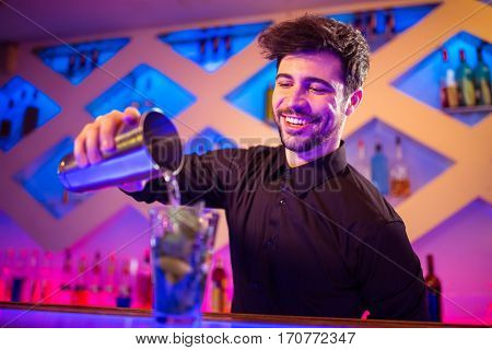 Handsome barkeeper pouring cocktail in glass at counter