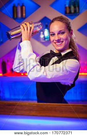 Portrait of young barmaid with cocktail shaker at illuminated counter