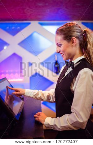 Side view of young barmaid smiling while using modern cash register at bar counter