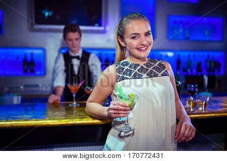 Portrait of smiling young woman standing against bartender at nightclub