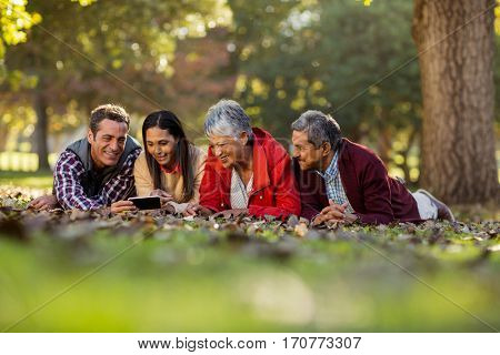 Family using mobile phone while lying on front at park