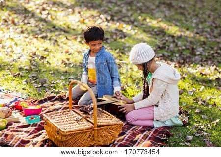 Siblings relaxing by basket at park