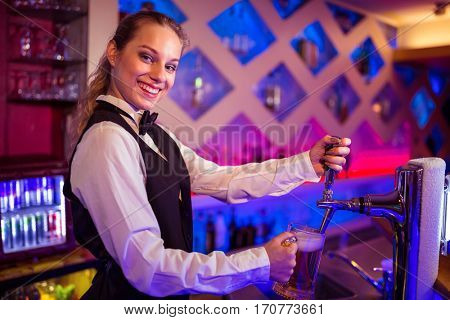 Portrait of happy barmaid pouring beer in glass at bar counter