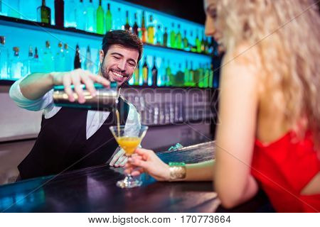 Barkeeper serving cocktail to young woman at counter in nightclub