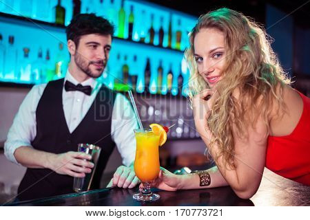 Portrait of beautiful woman leaning on counter while bartender in background at nightclub