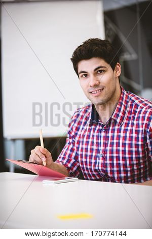 Portrait of smiling businessman writing on note pad
