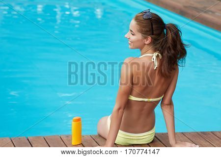 UV protection and suntan. Young pretty woman holding bottle with sunscreen lotion in swimming pool.