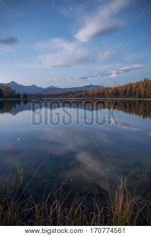Mirror Surface Lake Vertical Orientation Autumn Landscape With Mountain Range In Early Eveing With Stars On The Sky. Wild Nature Forest Water Scenery Photo With Calm Atmosphere Image.