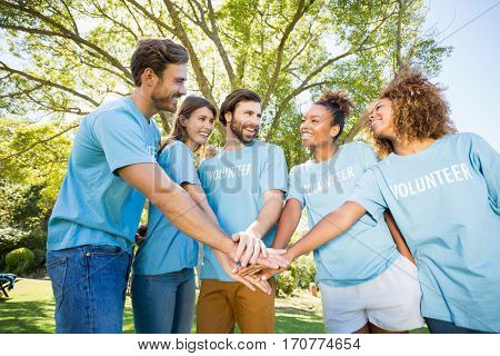 Group of volunteer forming hands stack in park