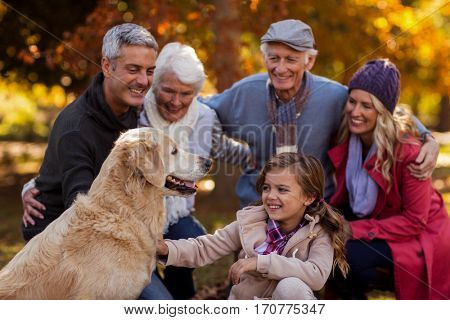 Cheerful multi-generation family with dog at park