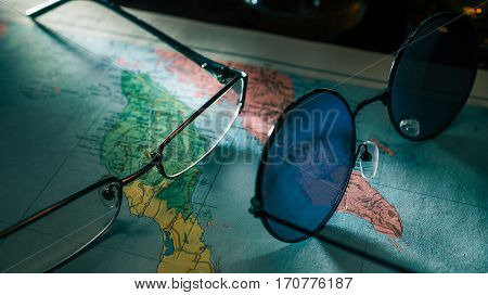 Sunglasses and spectacles on the page of old map atlas. Close-up view