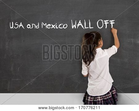 young political activist schoolgirl writing on school classroom blackboard Mexico and USA wall off with chalk in no border and land frontier between countries in protest concept