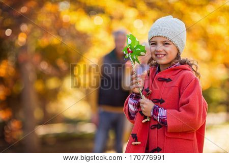 Portrait of cheerful girl with pinwheel toy standing at park