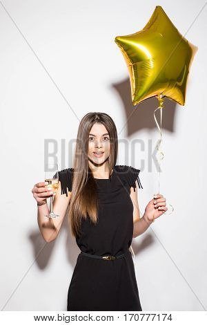 Happy attractive shocked young woman in black dress holding star shaped balloon and drinking champagne over white background