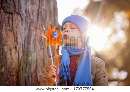 Cute boy blowing pinwheel while standing at park