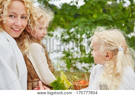Happy mother with two daugthers in autumn at park