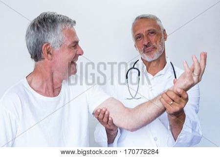 Male doctor giving palm acupressure treatment to senior man in hospital