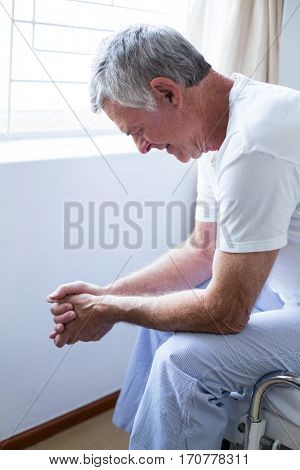 Upset senior man sitting on bed in bedroom
